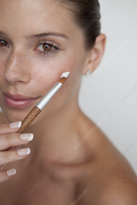 Woman holding brush with makeup