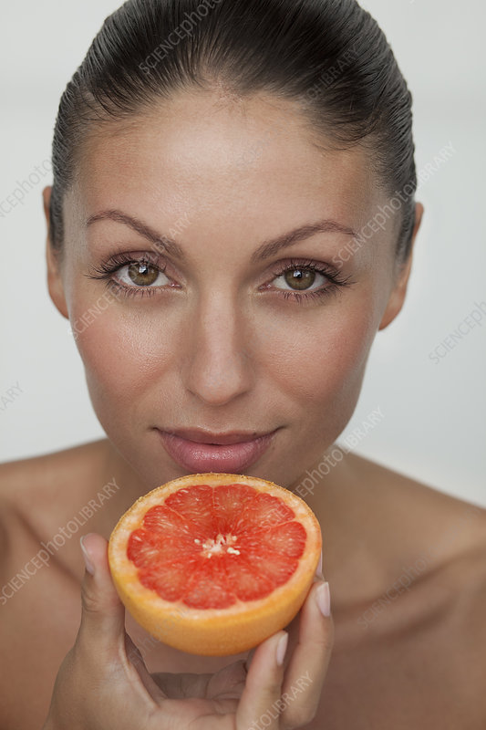Woman holding halved grapefruit