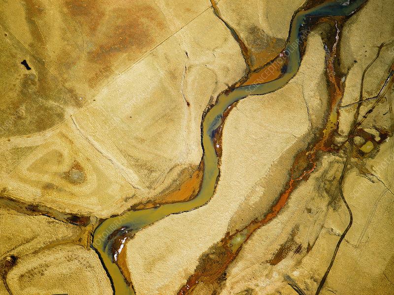 Dirty river through dry rural landscape