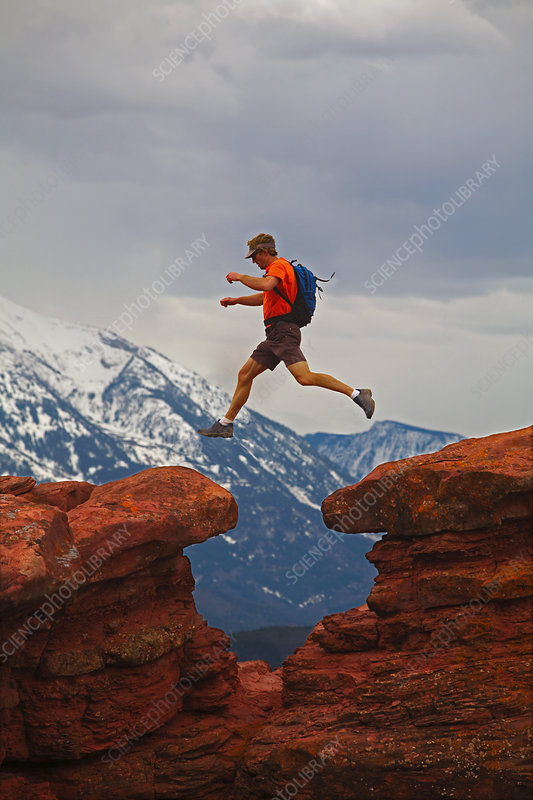 Hiker jumping between rocks
