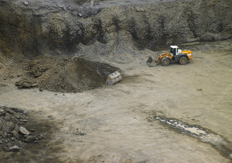 Bulldozer pushing sediment in quarry