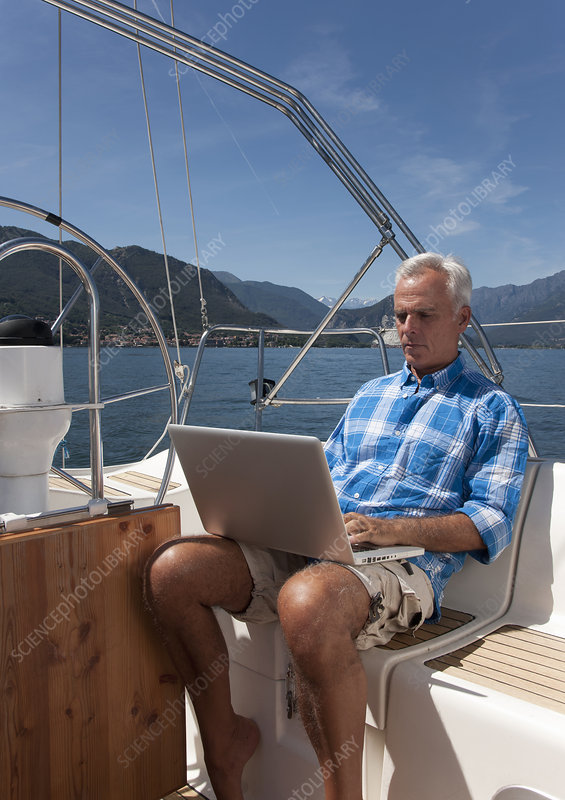 Older man using laptop on sailboat