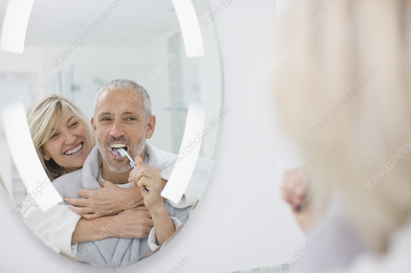 Man brushing his teeth with wife