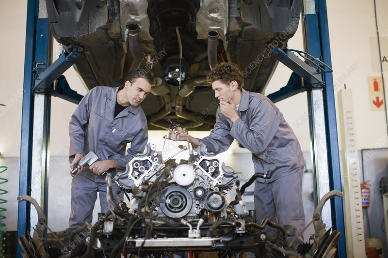 Mechanics working on car engine