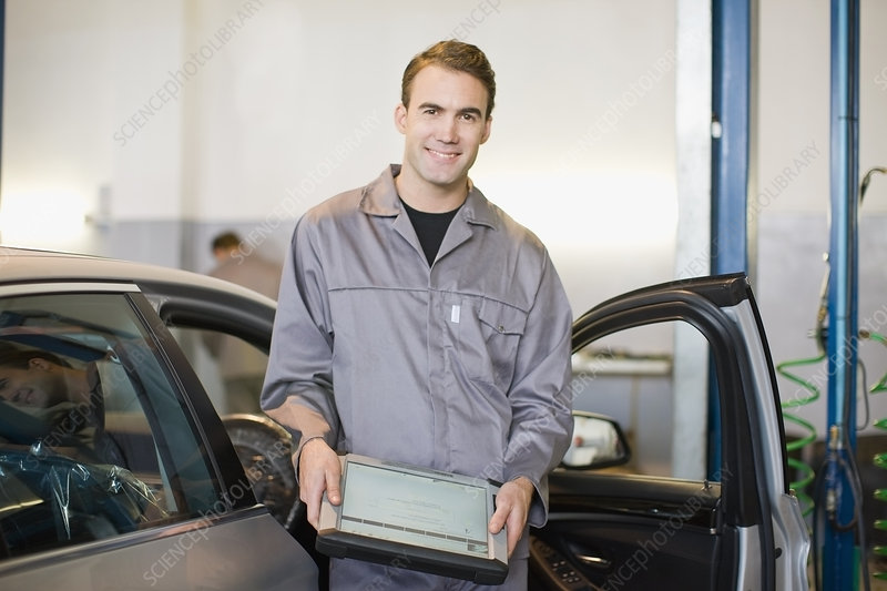 Mechanic with tablet computer in garage