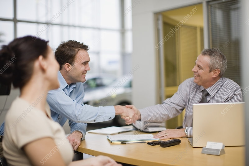 Couple shaking hands with car salesman