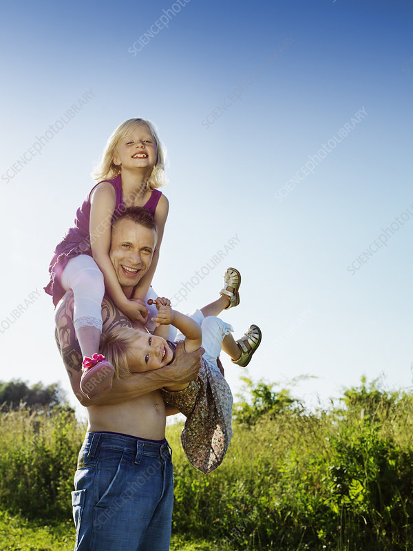 Father playing with daughters outdoors