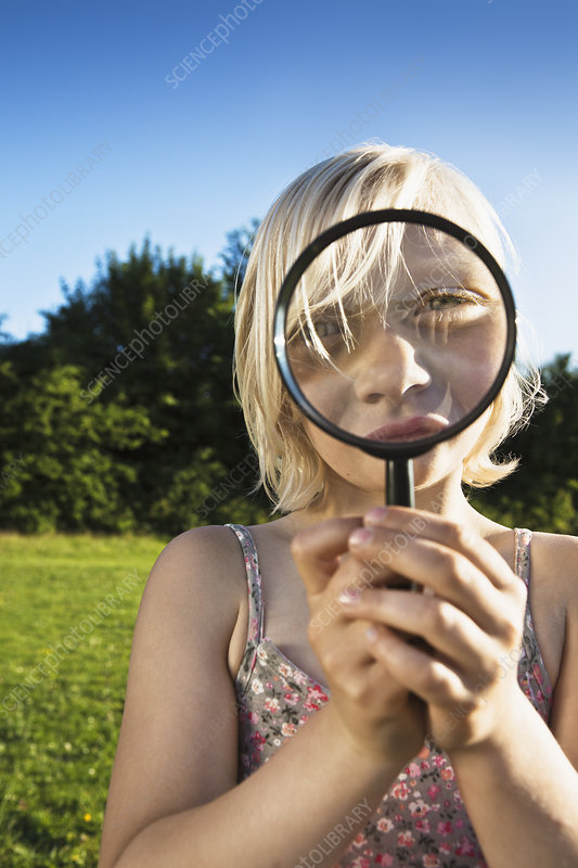 Girl playing with magnifying glass