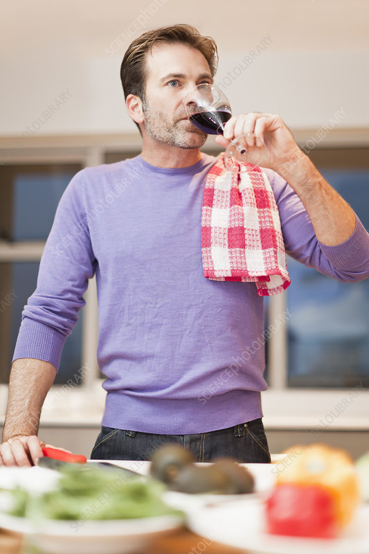 Man drinking wine and cooking dinner