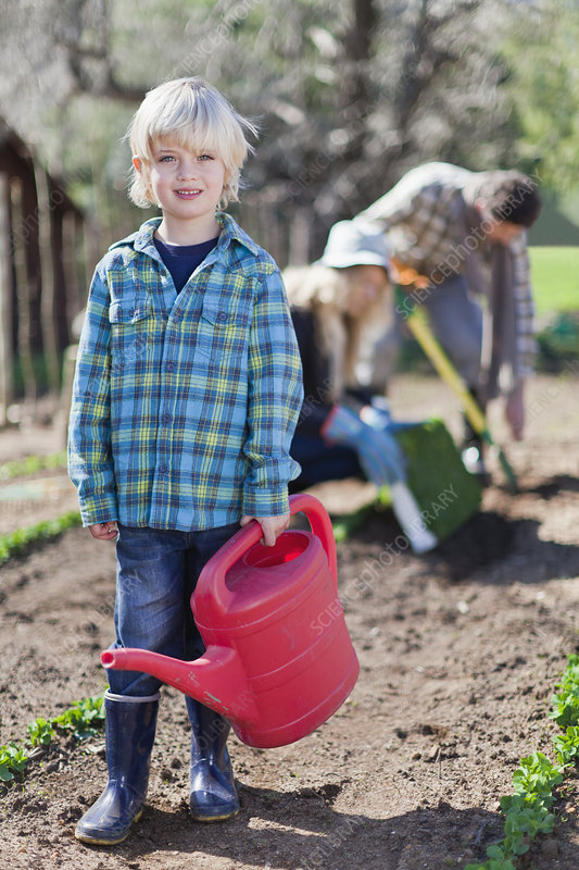 Boy carrying watering can in garden