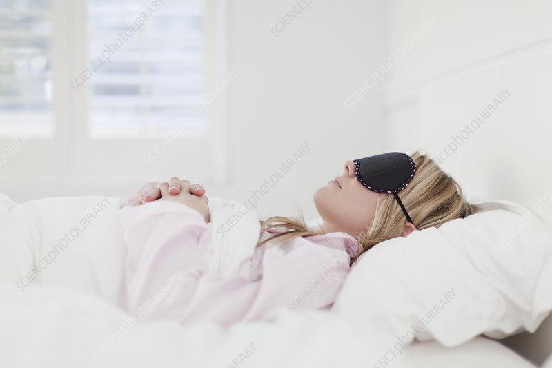 Woman in eyemask asleep in bed