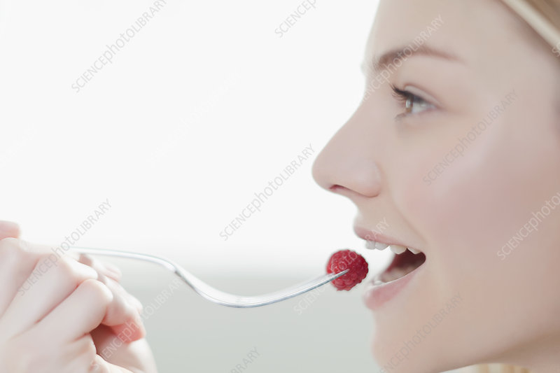 Smiling woman eating raspberry