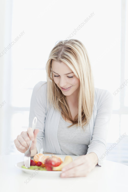 Smiling woman eating plate of food