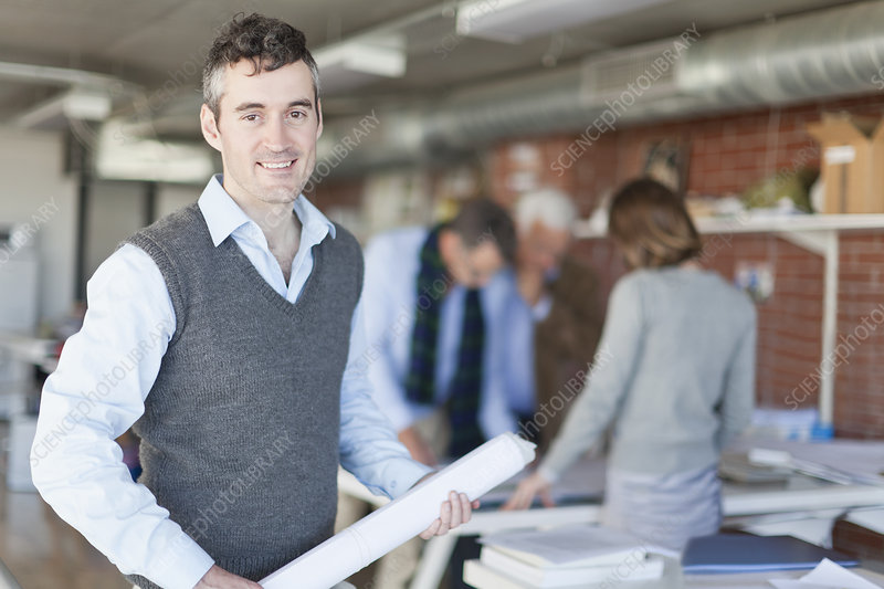Architect carrying blueprint in office