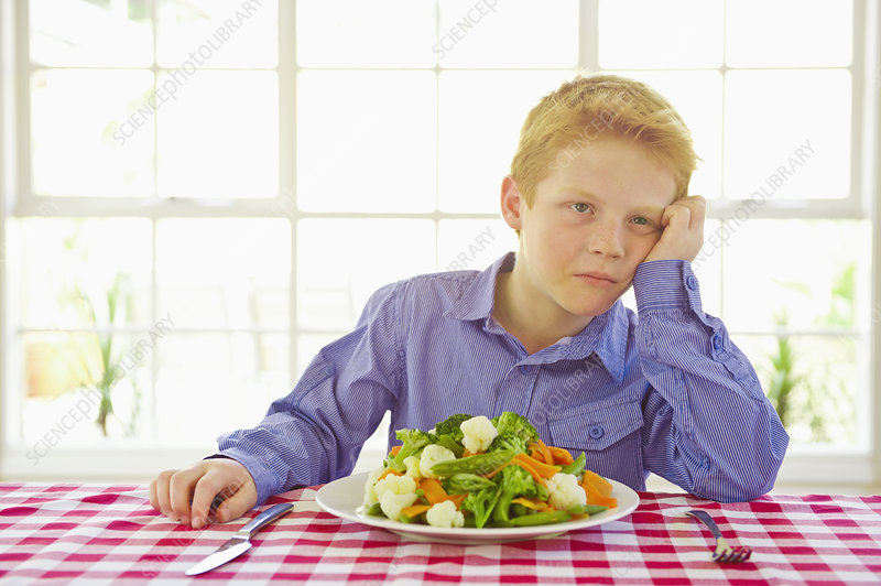 Frustrated boy with plate of vegetables