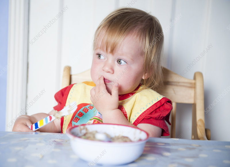 Toddler girl in bib eating at table