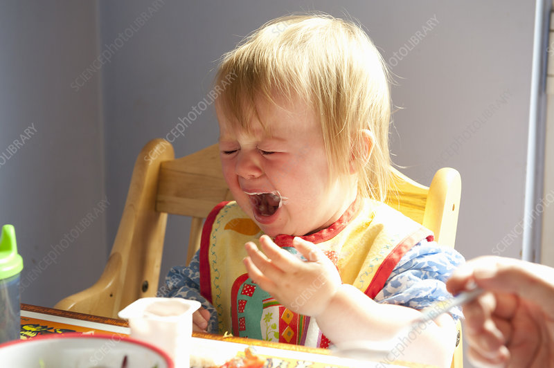 Toddler girl crying at table