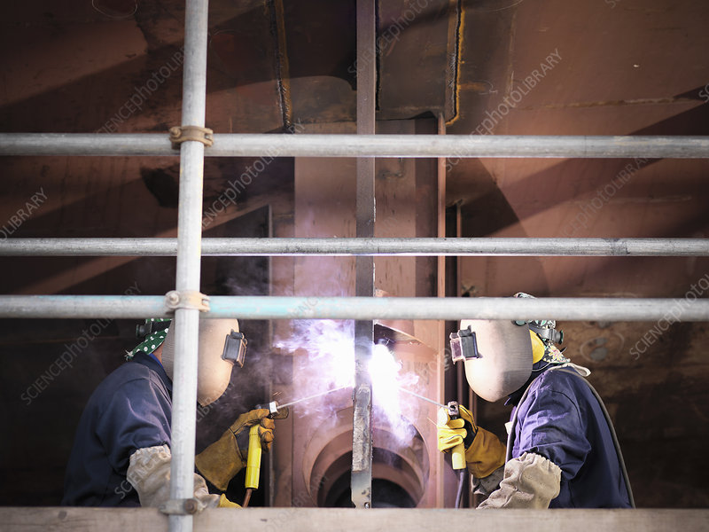 Welders at work building ship