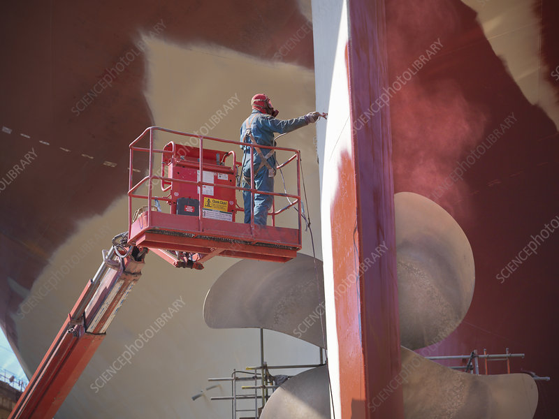 Worker painting ship's underside