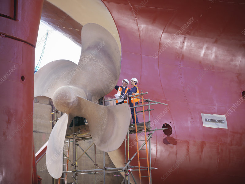 Workers examining ship turbines on site
