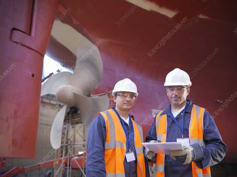 Workers standing on shipbuilding site