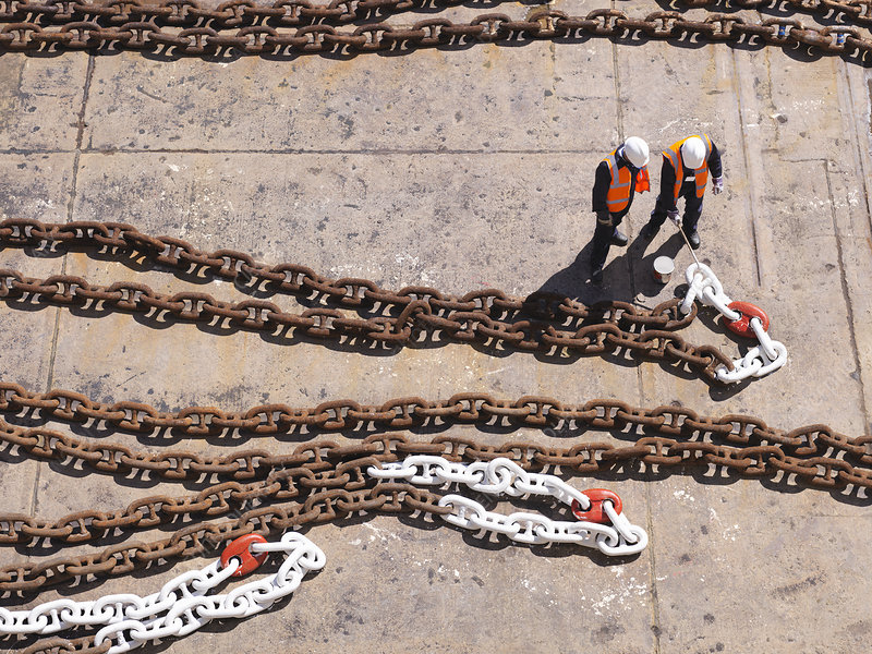 Aerial view of workers examining chain