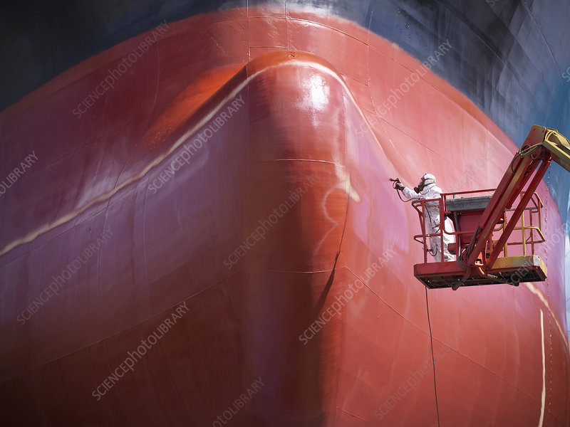 Worker painting ship's hull