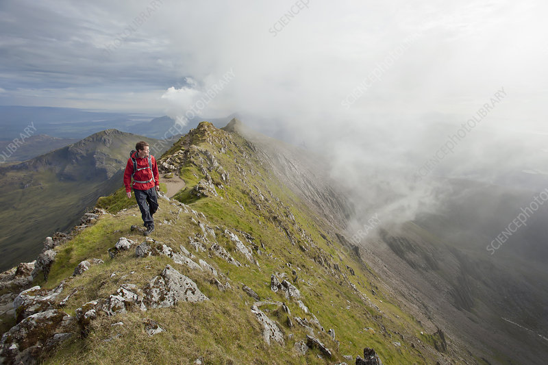 Hiker walking on rocky mountaintop