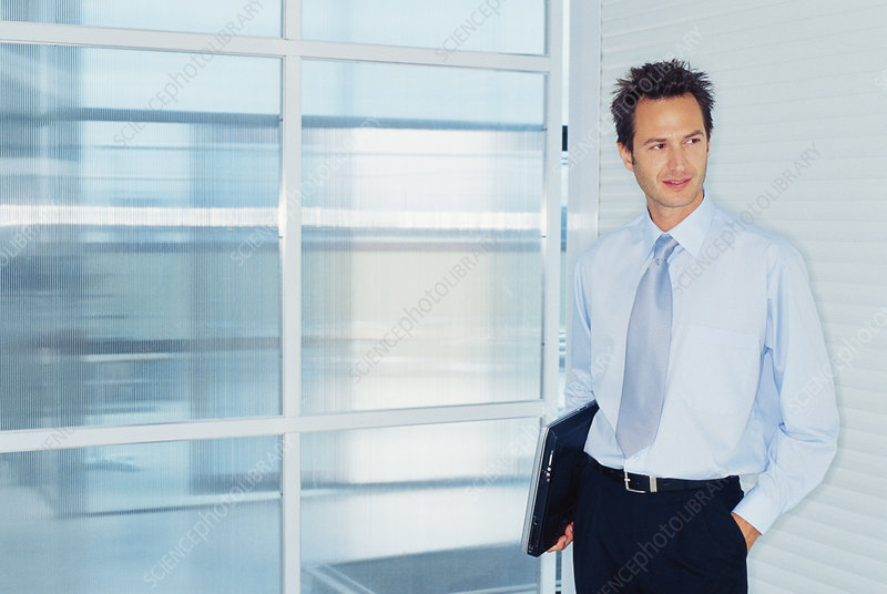 Businessman carrying laptop in office