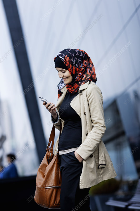 Woman in headscarf using cell phone