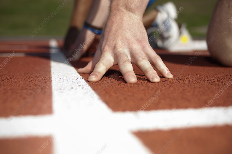 Close up of athlete's hand on track