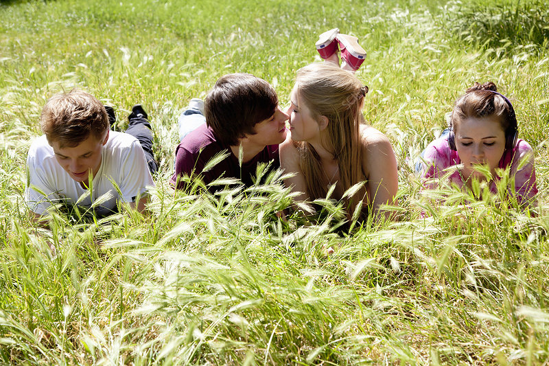 Teenagers ignoring kissing friends