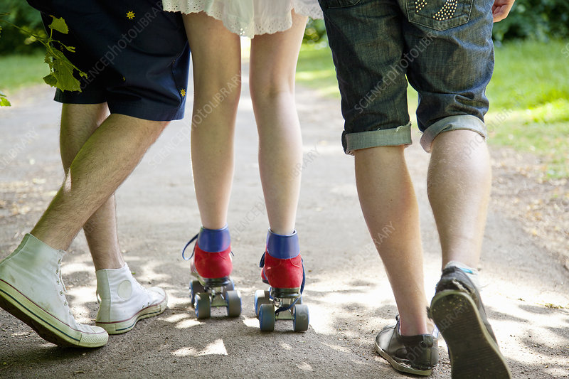 Teenage boys with roller skating girl