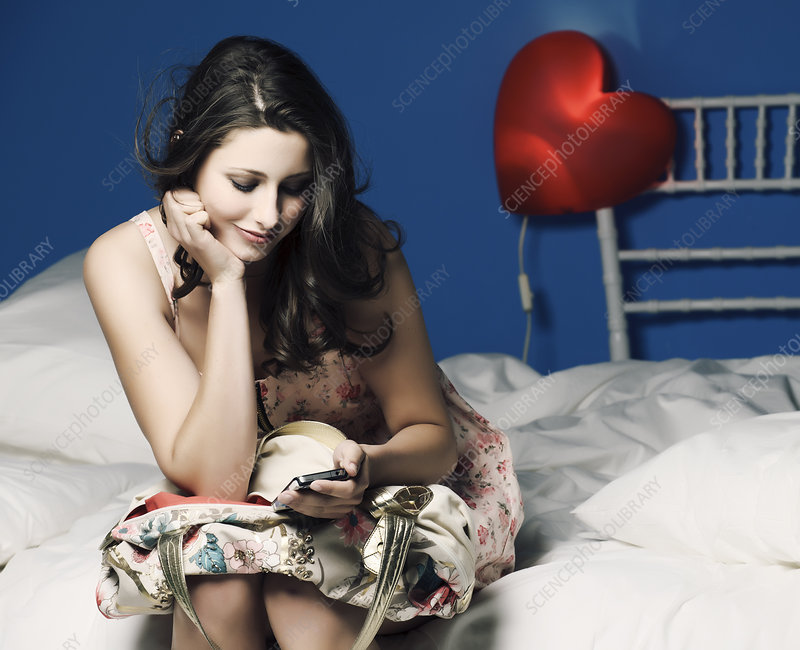 Teenage girl using cell phone on bed