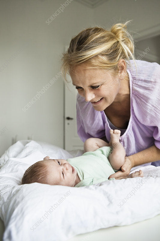 Mother changing infant's diaper