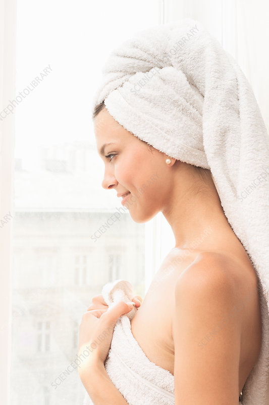 Smiling woman wrapped in towels