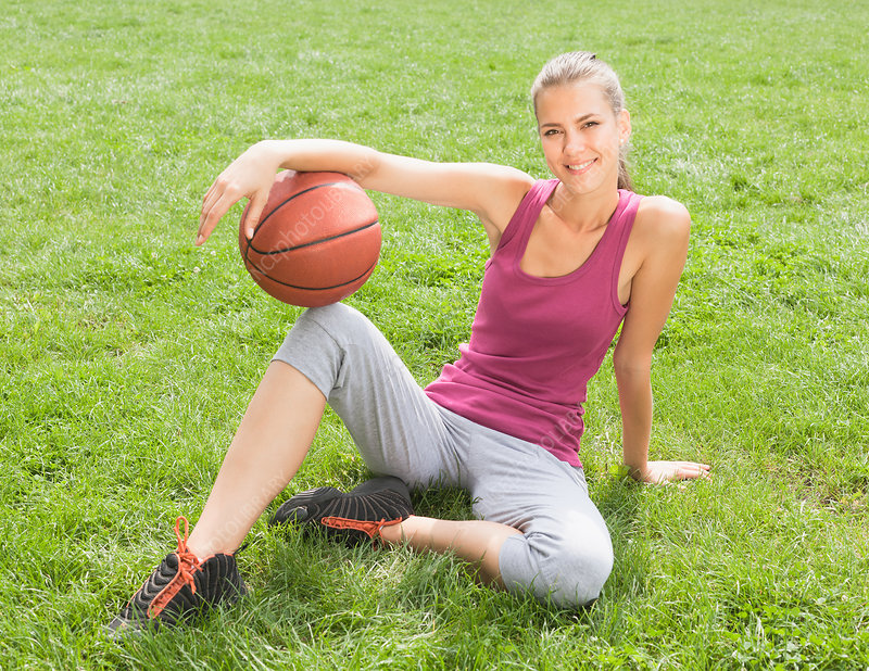 Woman holding basketball on grass