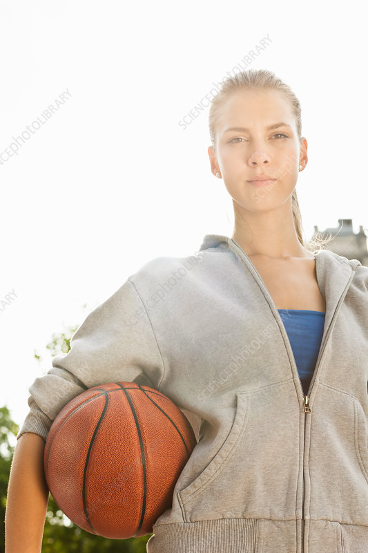 Woman carrying basketball outdoors