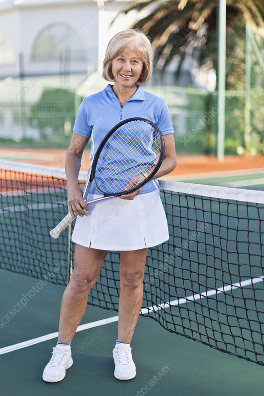 Older woman with tennis racket on court