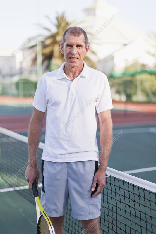 Older man with tennis racket on court