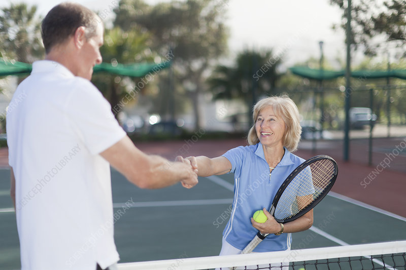 Older couple shaking hands on court