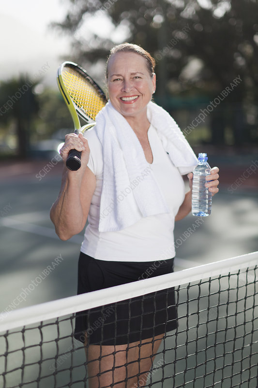 Older woman standing on tennis court