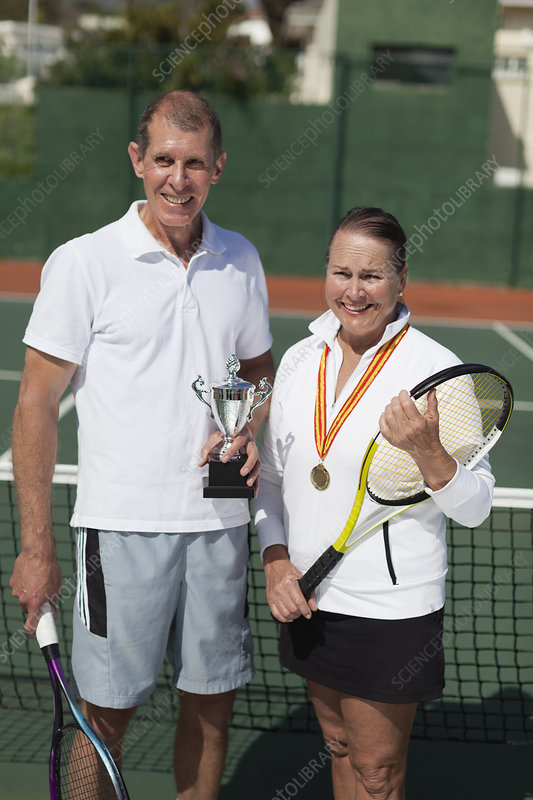 Older couple with trophy on tennis court
