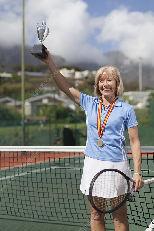 Older woman with trophy on tennis court