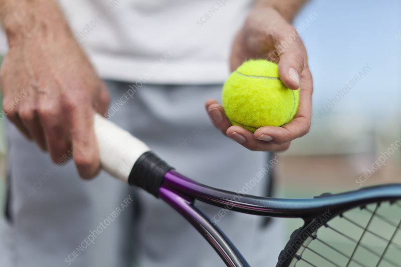 Older man holding tennis ball and racket
