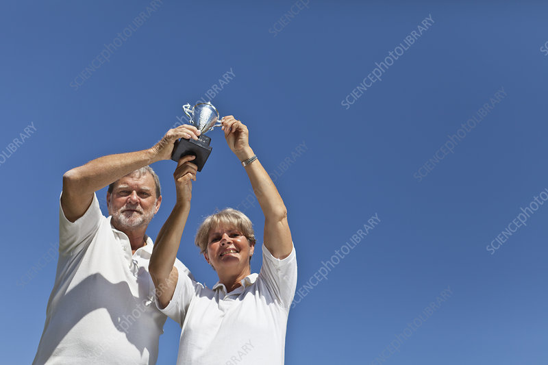 Older couple cheering with trophy