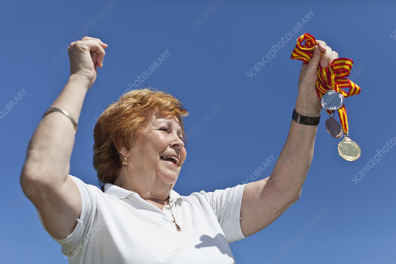 Older woman cheering with medals