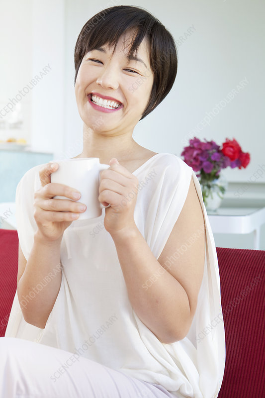 Smiling woman drinking cup of coffee