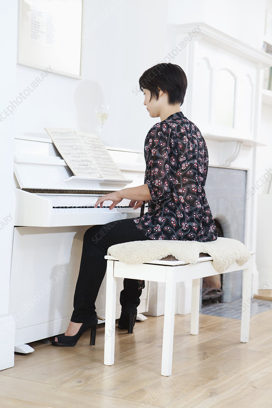 Woman playing piano at home