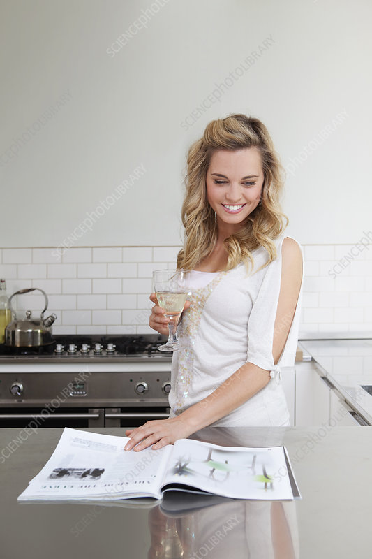 Woman relaxing with wine and magazine